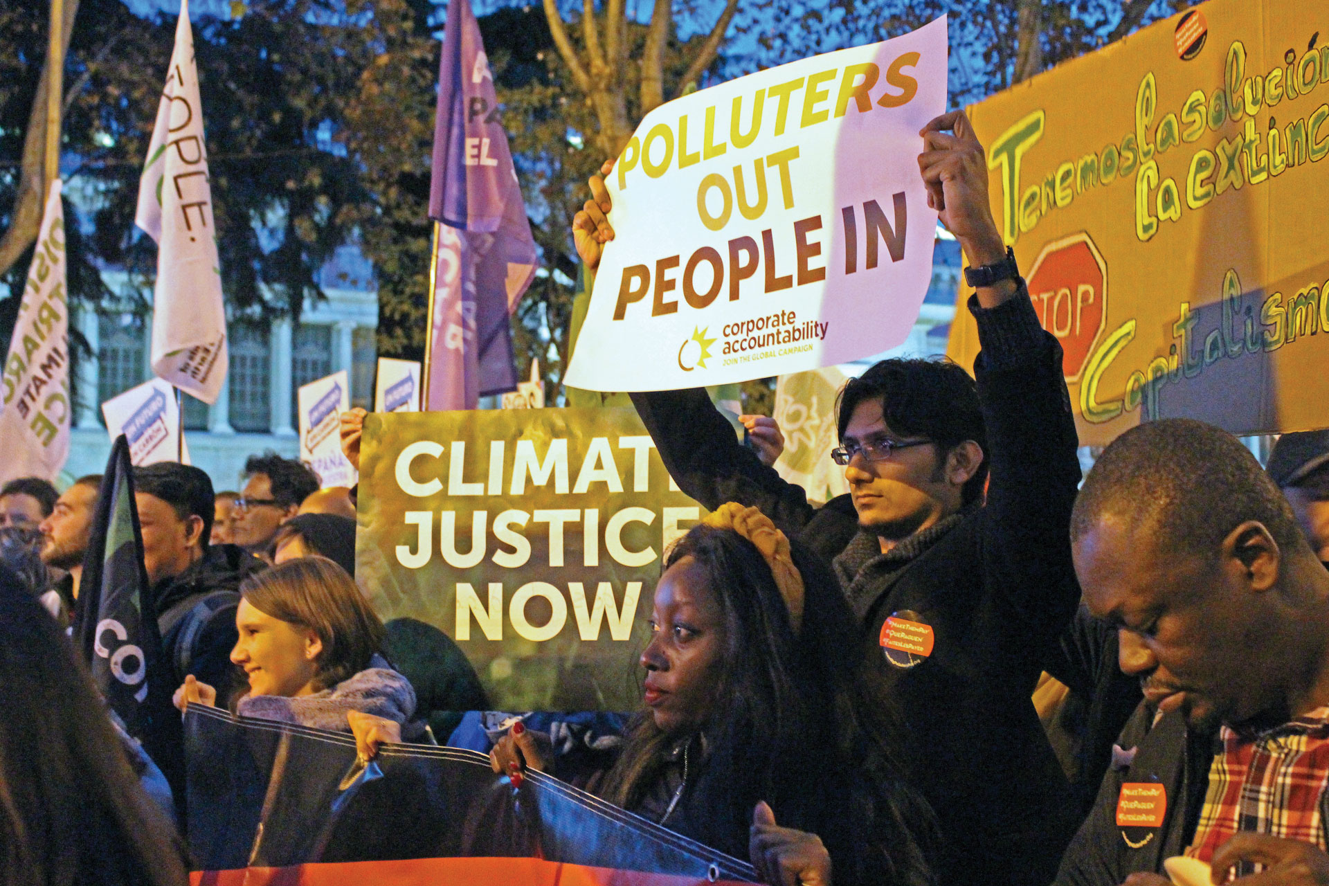 Protestors holding signs that say Climate justice and Polluters Out People In