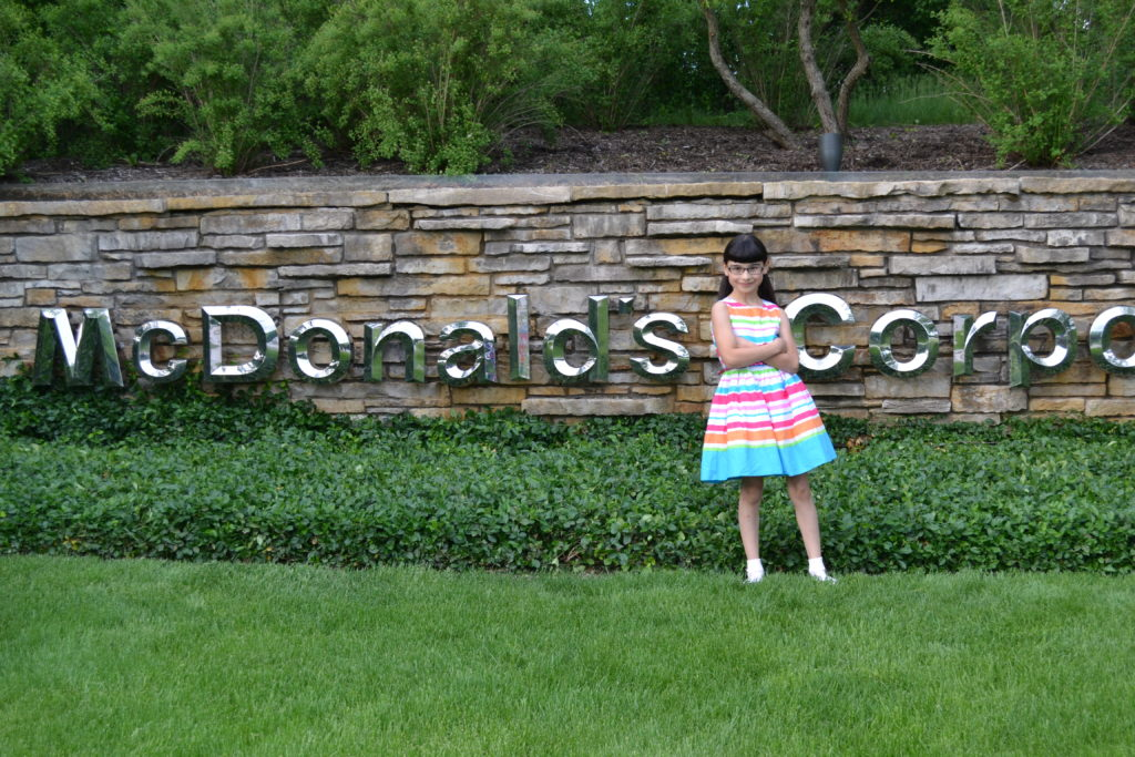 Hannah in front of McDonald's sign, demanding the corporation stop all harmful marketing practices to children.