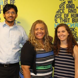 Public education champion Cecily Myart-Cruz poses with members of Corporate Accountability's food team (Deputy Campaigns Director Sriram Madhusoodanan and National Campaign Organizer Alexa Kaczmarski) in front of a mural in Corporate Accountability headquarters.