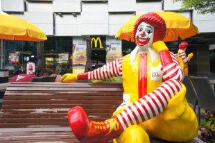 Statue of Ronald McDonald sits on a bench outside of a McDonald's in Bangkok, Thailand.