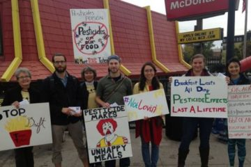 Organizers stand in front of McDonald's store with signs.