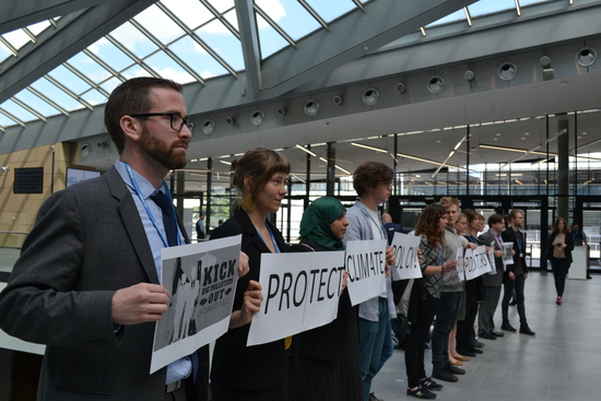 "The Federation of Young European Greens and other UNFCCC-accredited youth NGOs organized a silent protest outside the U.N. climate talks, spelling the message ""Protect climate policy! Kick big polluters out!"" Photo credit: Corporate Accountability International"