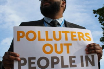 "Protester holds ""Polluters out, people in"" poster"