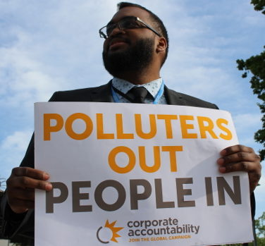 """Protester holds """"Polluters out, people in"""" poster"""