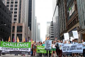 "Corporate Accountability International staff march with Rainforest Action Network"" down 6th Avenue"