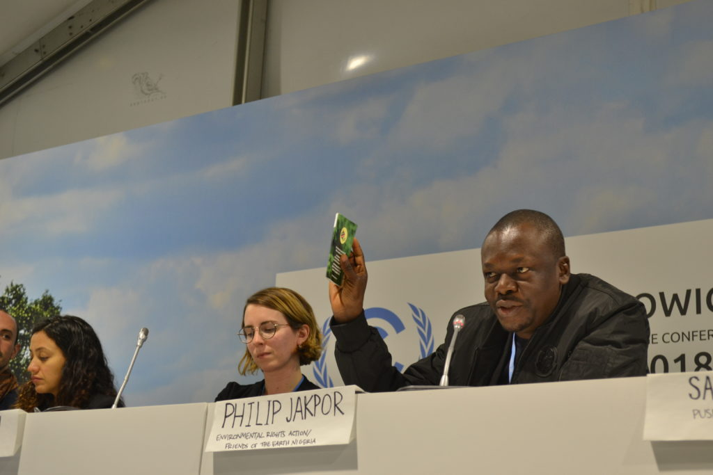 Philip Jakpor of ERA and FoENigeria holds up the Peoples Demands booklet at the official Fork in the Road UNFCCC side event.