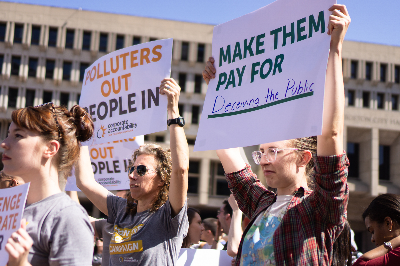 """Two people at a climate protest holding signs: """"Polluters Out, People In"""" and """"Make them pay for deceiving the public."""""""