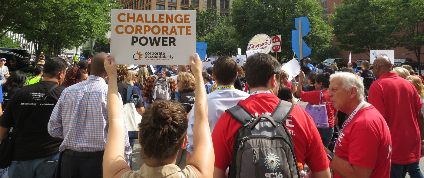 Sign reading 'Challenge Corporate Power'