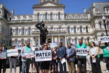A crowd of activists and councilmembers gathers in Baltimore to call for the passage of the Water Accountability and Equity Act.