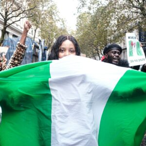 Woman in London holds up a Nigerian flag, standing in solidarity with the #EndSARS movement.