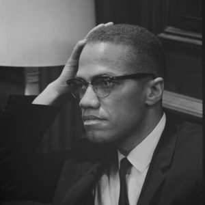 A black and white photo of Malcolm X resting his head against his hand.