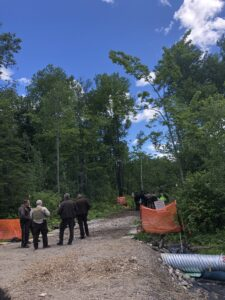 Four police officers stand huddled at one of the entrances to a Line 3 resistance camp in Minnesota.