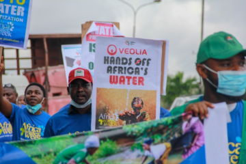 African water protectors march with signs rejecting water privatization